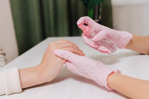 여성의 손을 닫습니다. 분홍색 고무 장갑을 낀 손은 손의 피부를 소독제로 처리합니다.