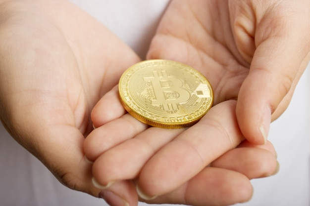 Female hands closeup with the coin bitcoin
