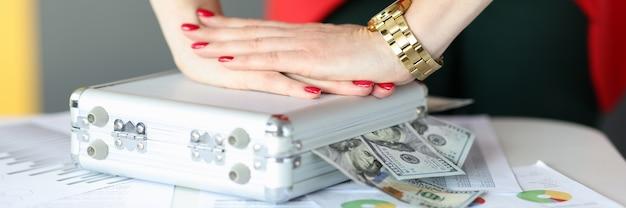 Женские руки закрывают чемодан с деньгами в офисе крупным планом, успешно ведя бизнес