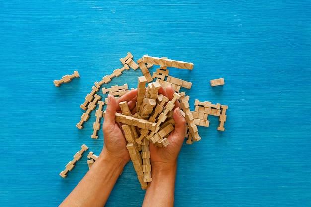Женские руки собирают детали деревянного детского конструктора на синем фоне