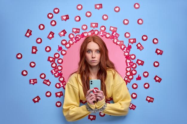 チェーンでスマートフォンガジェットに接続された女性の手、携帯電話デバイスに夢中になっている女性