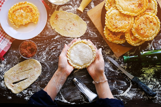 In the female hands of the cook is a pie, a cake of raw dough