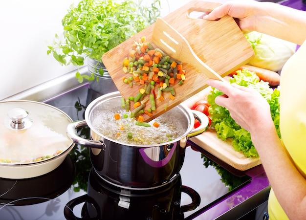 Женские руки готовят овощной суп на кухне
