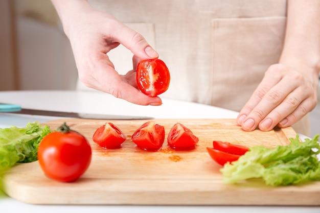 女性の手は、ジューシーな赤いトマトを木製のまな板の上でナイフで四分の一またはスライスに切ります。調理する前に野菜や材料を準備する方法。