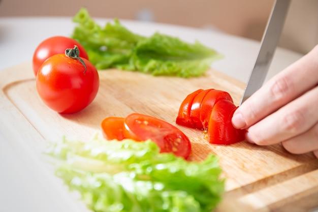 Женские руки ножом на деревянной разделочной доске нарезают сочный красный помидор ломтиками. способ подготовки овощей и ингредиентов перед приготовлением.