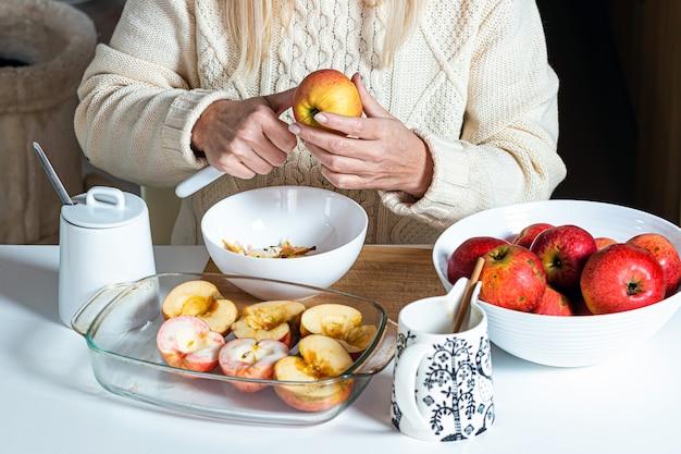 女性の手がリンゴを切って、それを焼く準備をします。リンゴの入った白いボウルのテーブルの上で、休日のための自家製のベーキングコンセプト