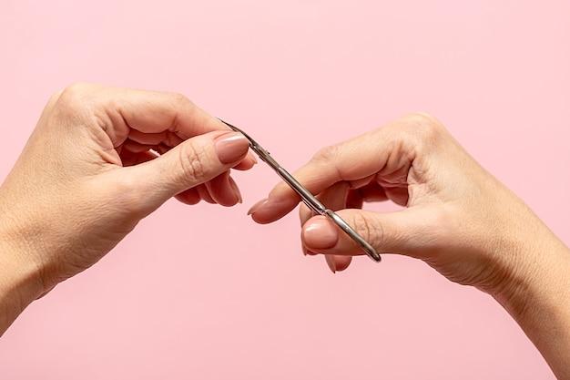 Женские руки стригут ногти маникюрными ножницами на розовом