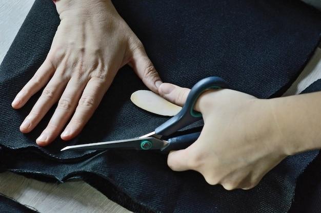 Женские руки разрезают ножницами черную ткань. крупный план.