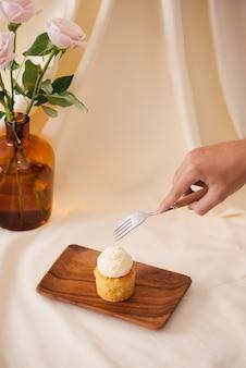女性の手がテーブルの上のおいしいカップケーキをカットします