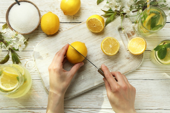 mani femminili taglia il limone per fare la limonata su fondo di legno bianco
