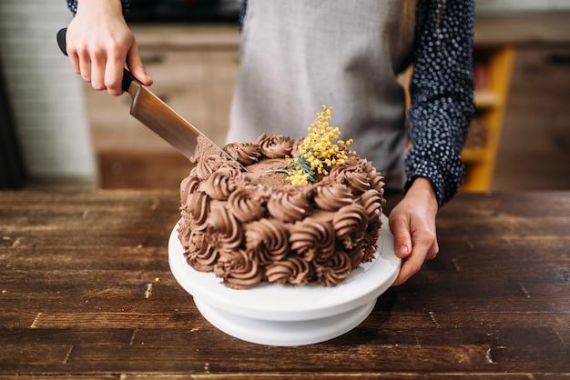 Женские руки резка шоколадного торта ножом, кулинарный шедевр