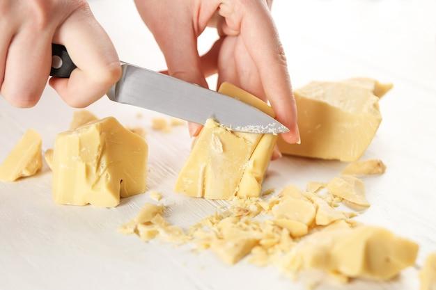 ココアバターを切る女性の手、クローズアップ
