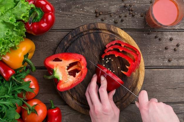 여성 손 절단 후추 테이블, 평면도. 상추, 후추, 토마토 주스 한 잔, 나무 판자 및 칼의 테이블 잎