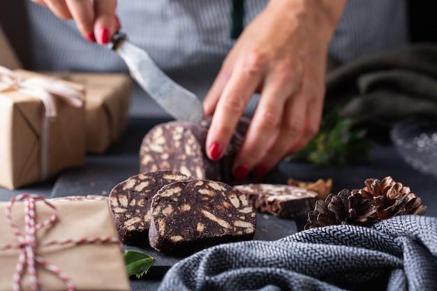 伝統的なイタリアのデザートクリスマスチョコレートサラミを切る女性の手