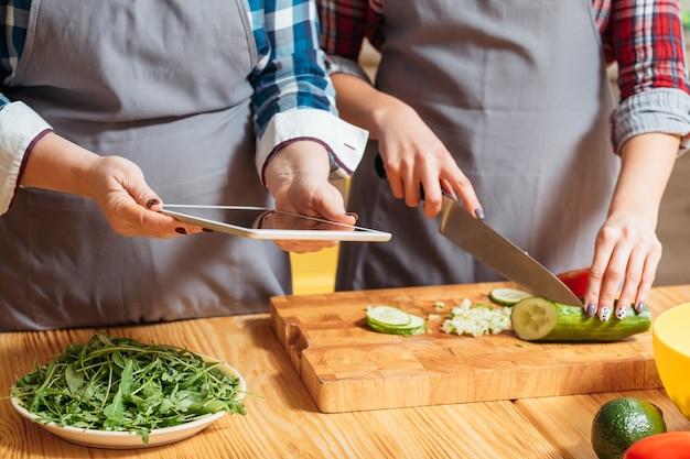 Женские руки, режущие овощи для салата на кухне
