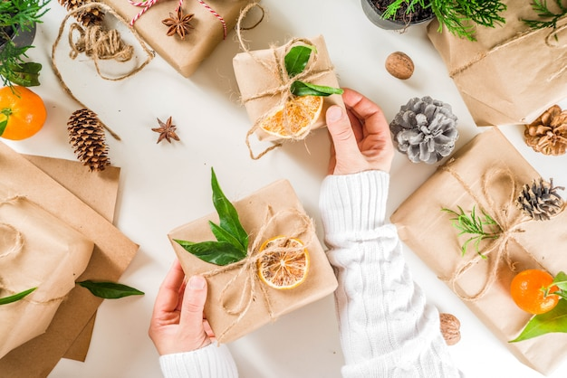 Female hands decorate christmas gift box.