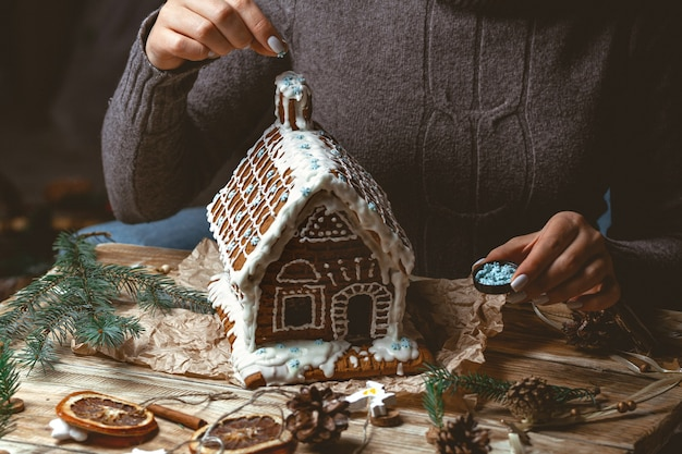 Female hands decorate the christmas gingerbread house