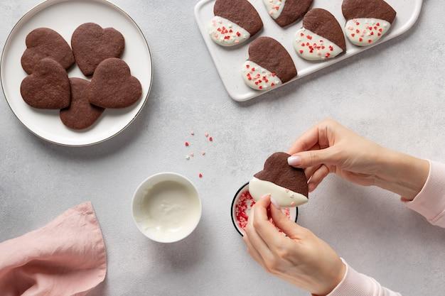 女性の手がハート型のクッキーを飾る