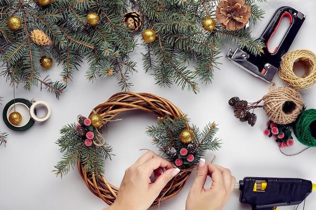 Женские руки украшают новогодний венок еловыми ветками с красной ягодой и лесными шишками, ...