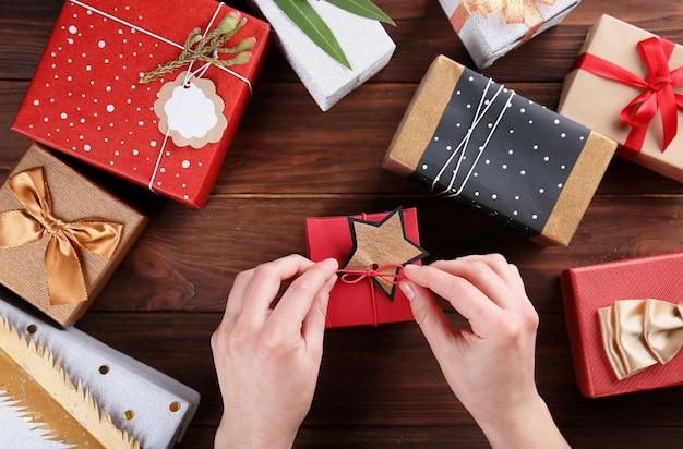 Женские руки, украшающие подарки на деревянном столе