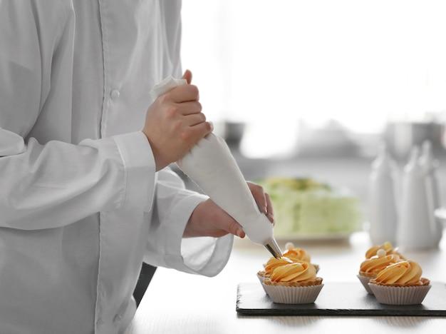 Женские руки украшают пироги кремом.