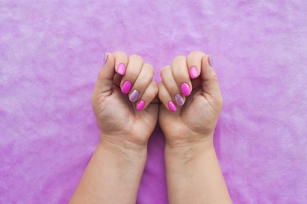 女性の手はライラックテキスタイルの表面に美しいライラックマニキュアを示しています