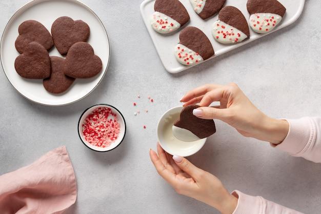 女性の手がチョコレートクッキーのハートを溶かしたホワイトチョコレートに浸します