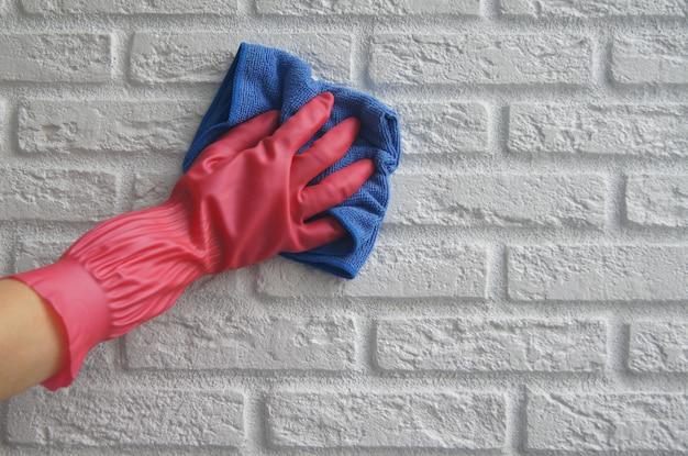 女性の手はピンクのゴムで白い壊れた壁のハンドルを消毒または洗浄します。クリーニングサービス。covid-19中のコロナウイルス感染の予防