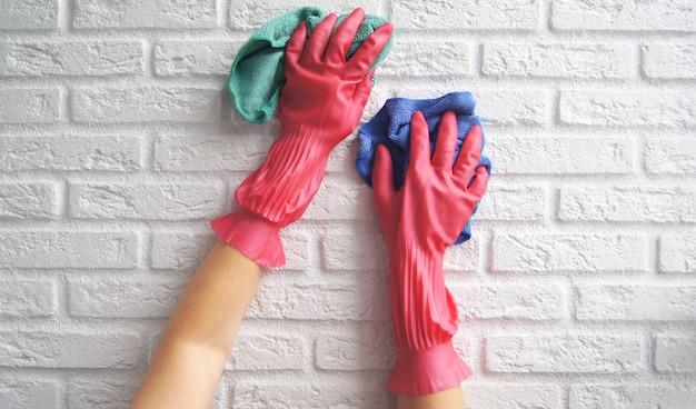 女性の手は白い防壁の消毒または洗浄