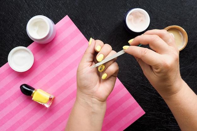 Женские руки делают маникюр. на черном столе баночки с кремом, лаком и розовая салфетка.