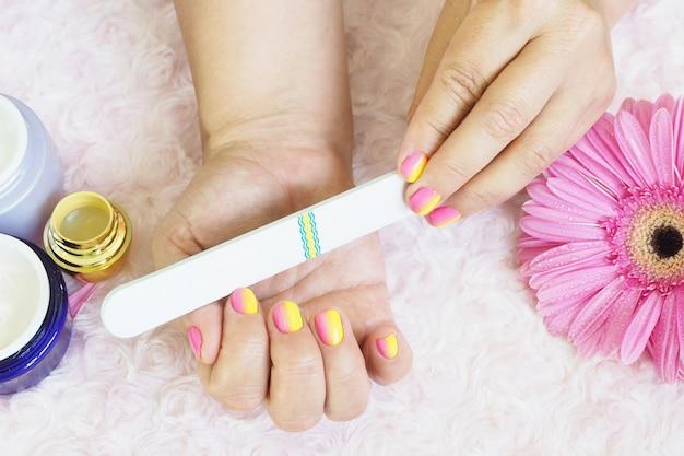 Женские руки делают маникюр. баночки с кремом, пилочка для ногтей, гербера с каплями воды на светло-розовом плюше