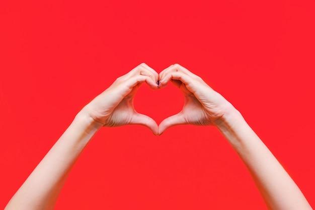 Женские руки делают форму сердца, изолированные на красном фоне