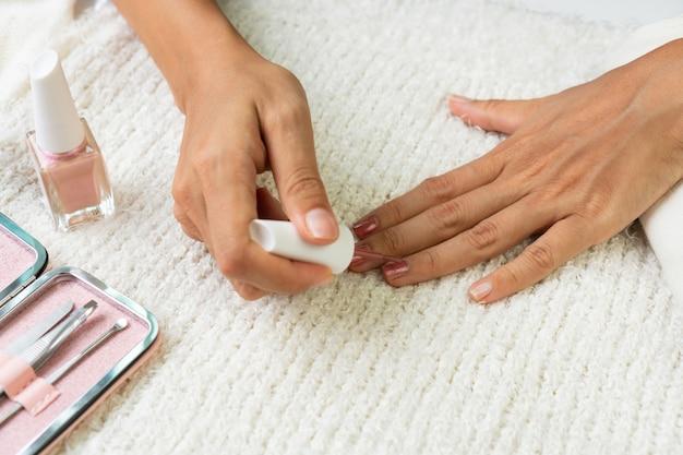 Женские руки делают лак для ногтей красного жемчужного цвета с набором маникюрных инструментов и инструментов