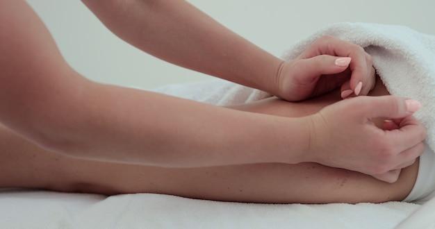 편안한 엉덩이 마사지를 하는 여성의 손을 닫습니다. 여성 마사지 치료사는 전문적으로 허벅지를 마사지합니다. 미용 치료 개념입니다.