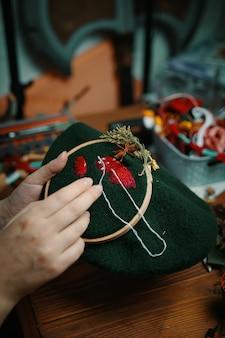 Женские руки делают вышивку шляпки-гриба в деревянном пяльце на зеленом материале вышивкой.