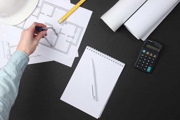 여성의 손은 검은 색에 건물 계획을 그립니다.