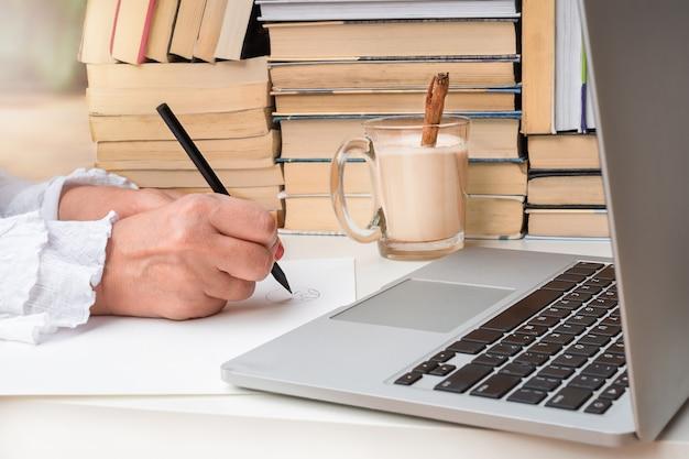 여성의 손은 컴퓨터와 책 근처 종이에 연필로 그립니다.