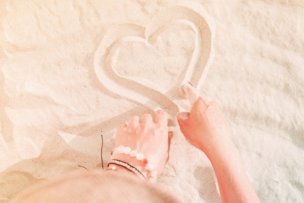 Female hands drawing heart on sand closeup