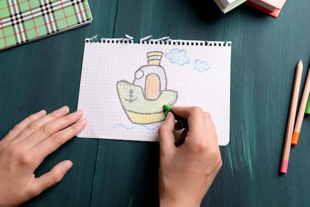 木製のテーブルの背景に紙に絵を描く女性の手