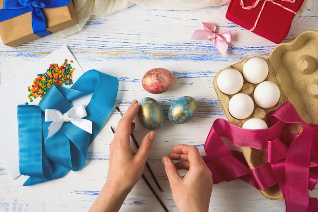 Female hands during painting easter eggs, ribbons, colorful colors, gifts on a white wooden table