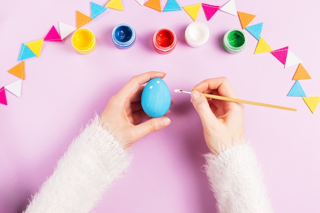 Female hands in a fluffy white sweater paint easter eggs with a brush and paints