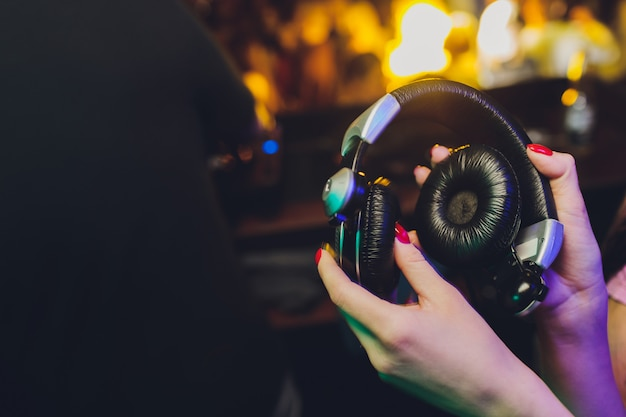 Female hands fold folding stereo headphones on a club background.