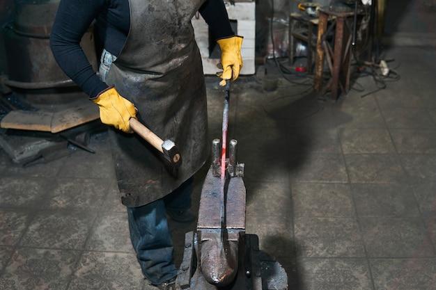 女性の手は、伝統的な鍛造でアンビルに溶銑ワークピースを鍛造します