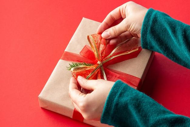 Женские руки из угла завязывают бант на рождественский подарок на красном
