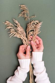 女性の手は、緑の背景に乾いた草の耳に優しく触れます。垂直方向のビュー