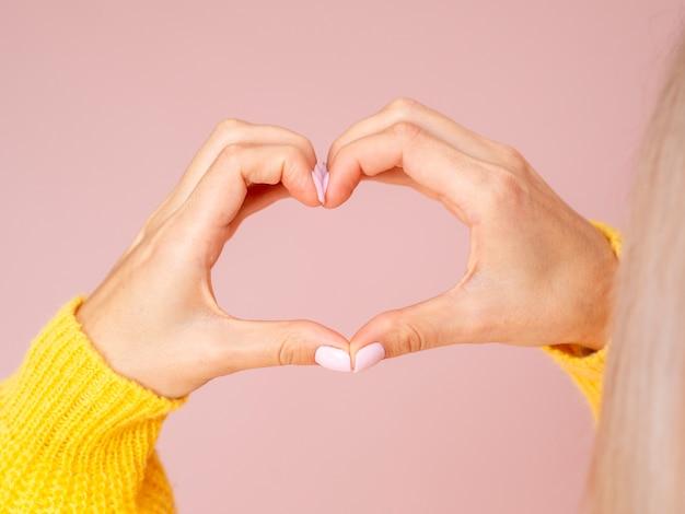 Female hands gesturing heart