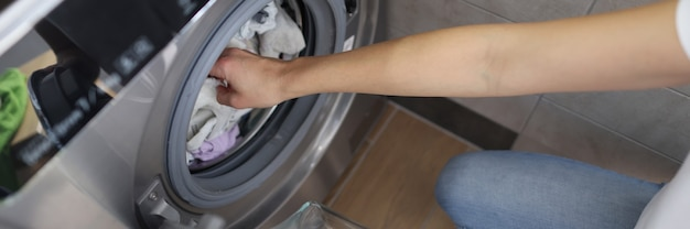 Female hands getting out clean clothes from washing machine in bathroom