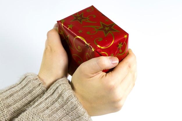 흰색 배경에 고립 된 크리스마스 선물을주는 여성의 손