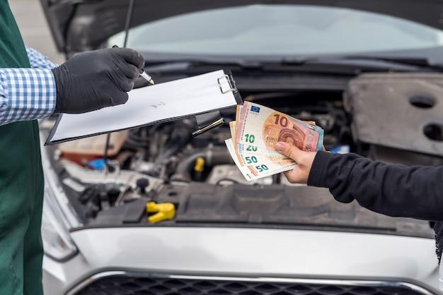 자동차 서비스에 대 한 유로 지폐를주는 여성 손
