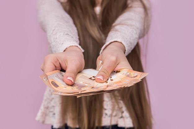 분홍색 벽에 유로 지폐를주는 여성 손